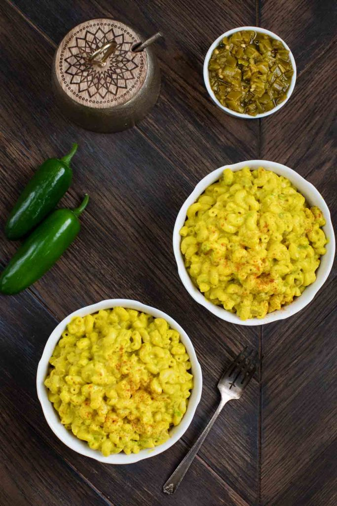 An overhead shot of 2 bowls of green chile mac and cheese on a wooden background.