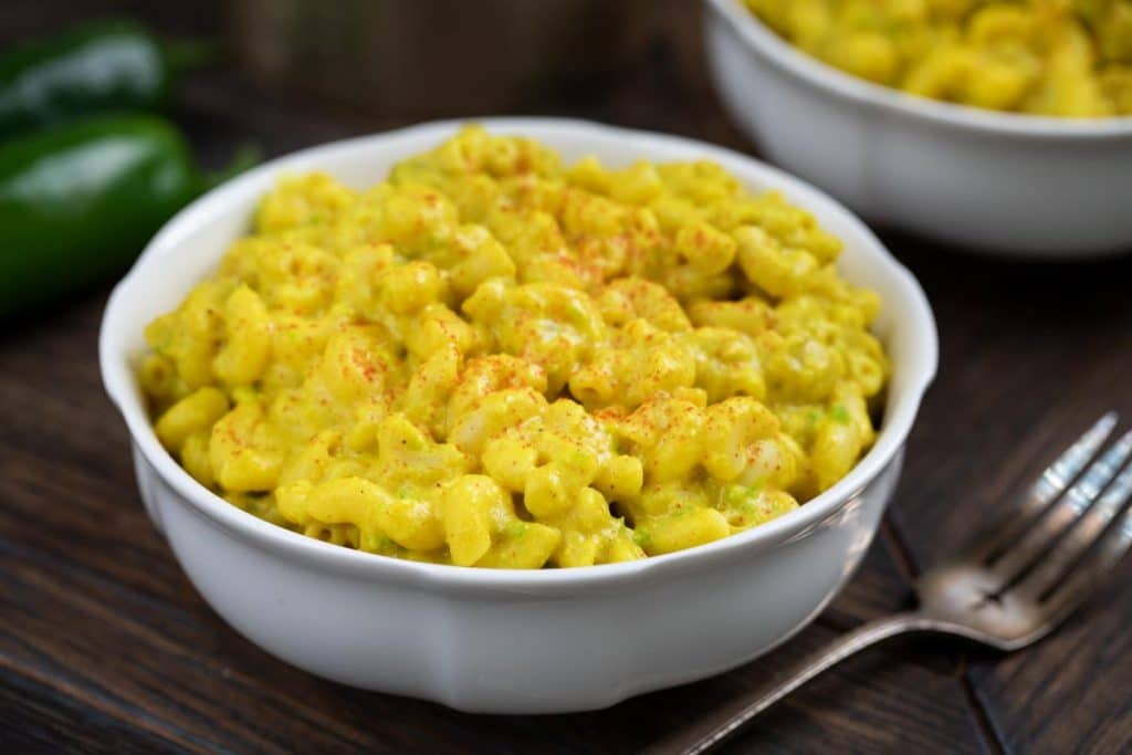 A white bowl of Green Chile Mac and Cheese, sprinkled with cayenne pepper with a fork on the side.