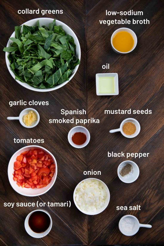 An overhead shot of the ingredients for collard greens, including collard greens, vegetable broth, garlic, paprika, mustard seeds, tomatoes, black pepper, salt, soy sauce and onion.