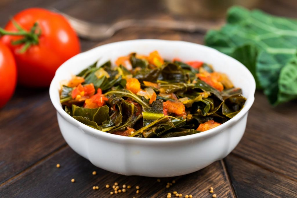 Instant Pot Collard Greens in a white bowl with tomatoes and fresh greens in the background.