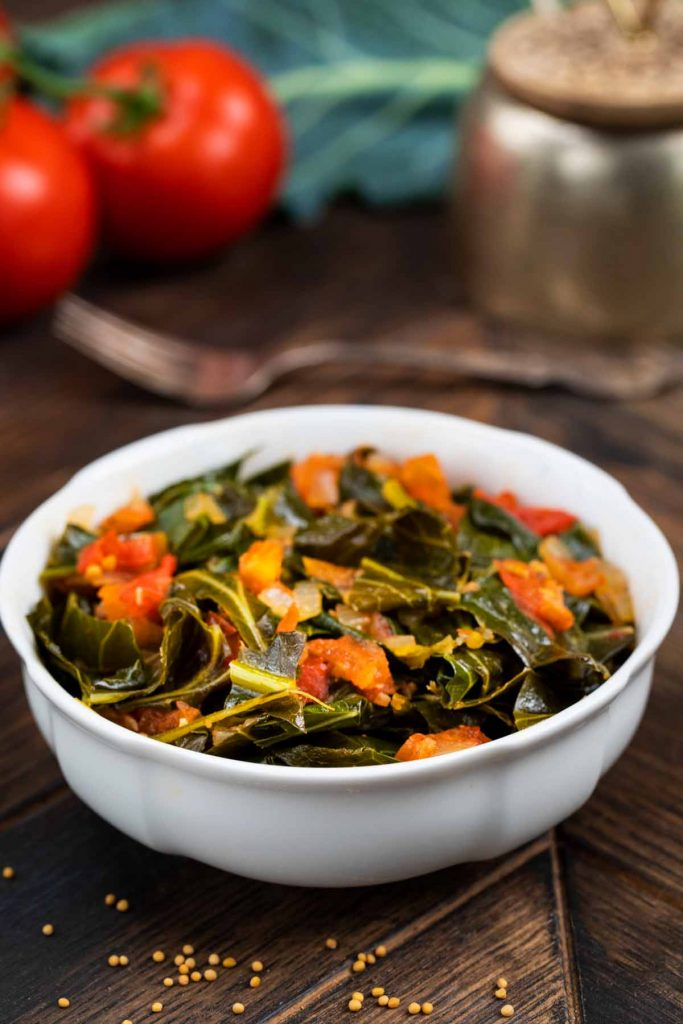 A white bowl of cooked collard greens with tomatoes, with mustard seeds sprinkled on the side.