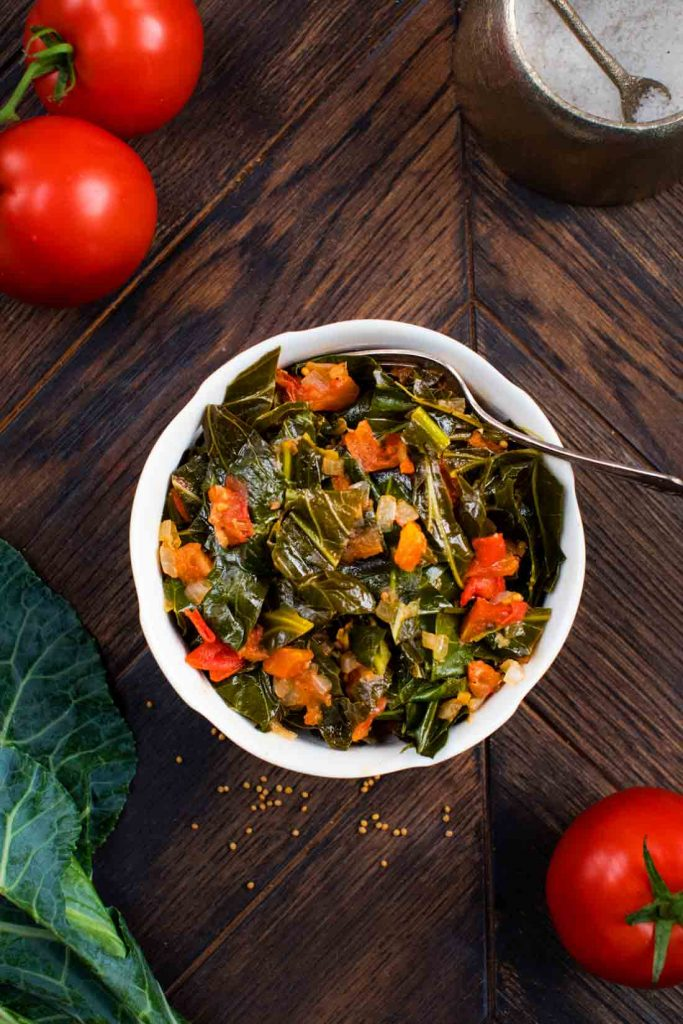 An overhead photo of a bowl of cooked collard greens, with fresh tomatoes and collard green leaves on the side.