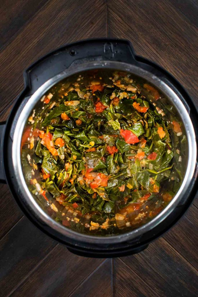 An instant pot filled with collard greens and tomatoes.