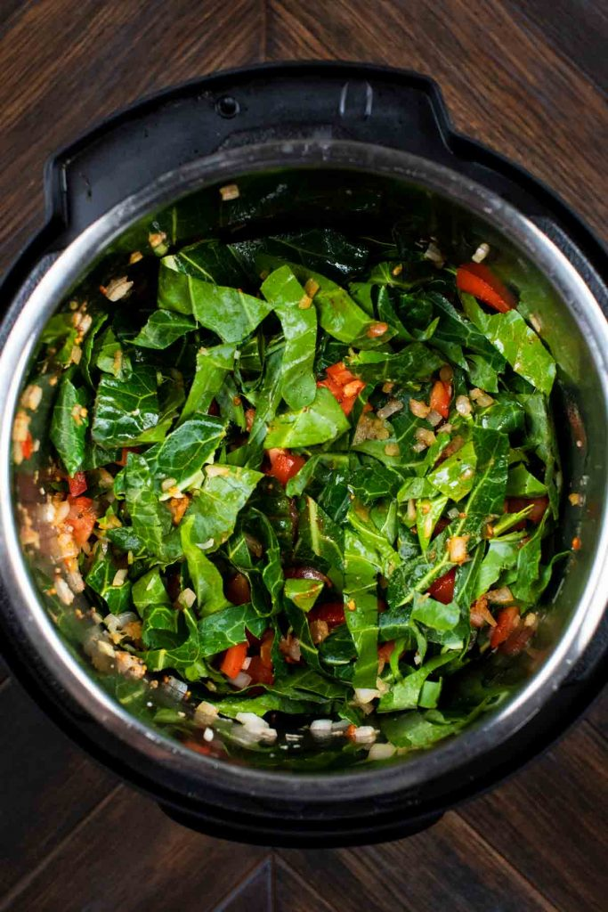 A pressure cooker filled with tomatoes, soy sauce, onion, garlic, and collard greens.