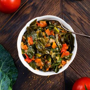 An overhead shot of a bowl of cooked collard greens with tomatoes and salt on the side.