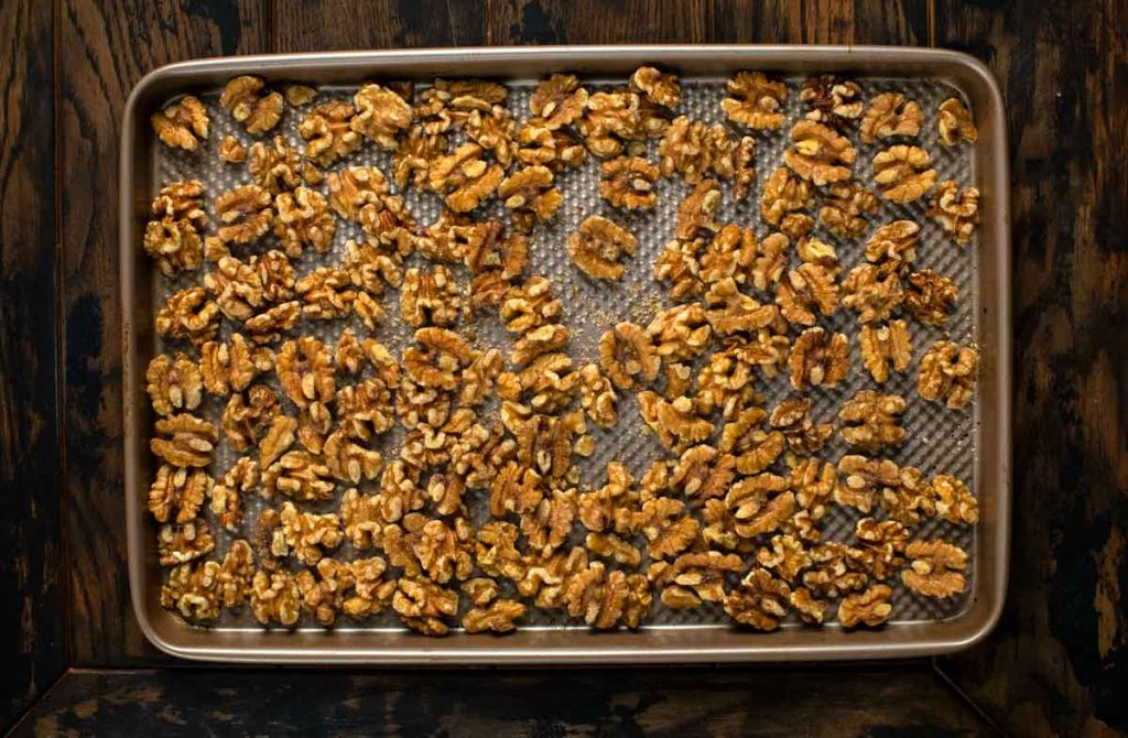 An overhead shot of a baking sheet covered in walnuts.