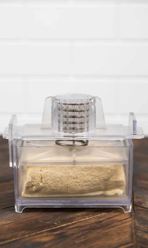 A tofu press with a tofu block inside.