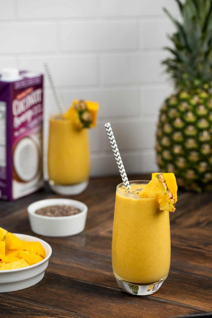A photo showing a glass of tropical chia seed smoothie with a straw, with a small bowl of chia seeds, and chopped mango.