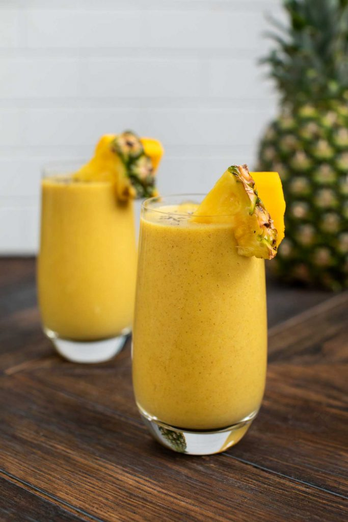 2 glasses of tropical chia seed smoothie with fresh pineapple and mango on the sides of the glasses.