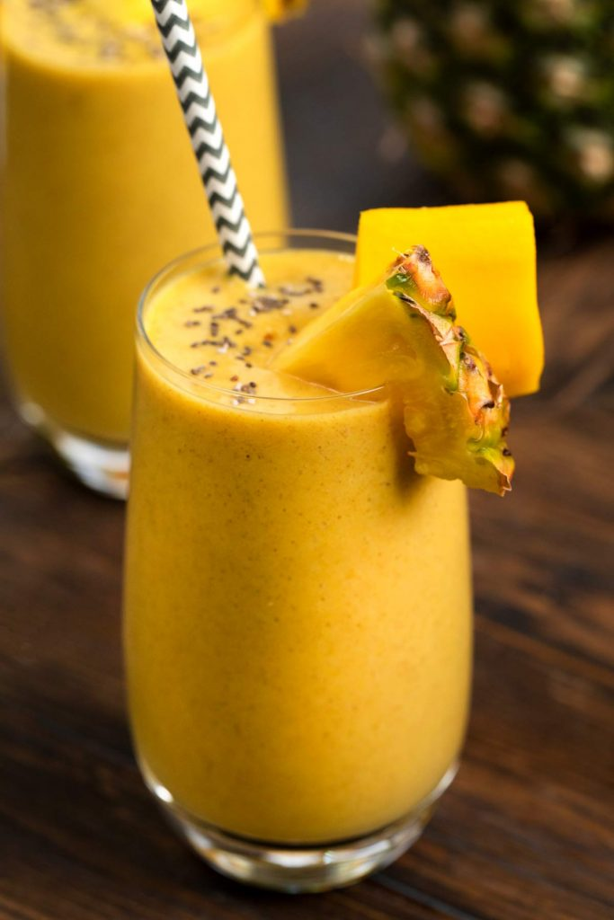 A closeup photo of a glass filled with a tropical chia seed smoothie, topped with fresh pineapple, mango, chia seeds and a straw.