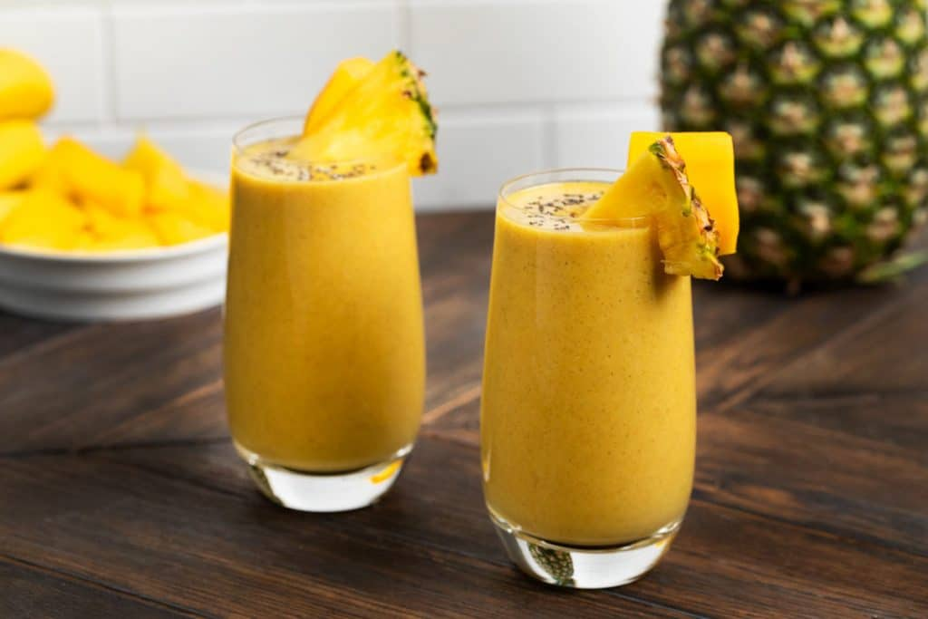 2 tropical smoothies in glasses with a whole pineapple and pieces of pineapple and mango in the background.
