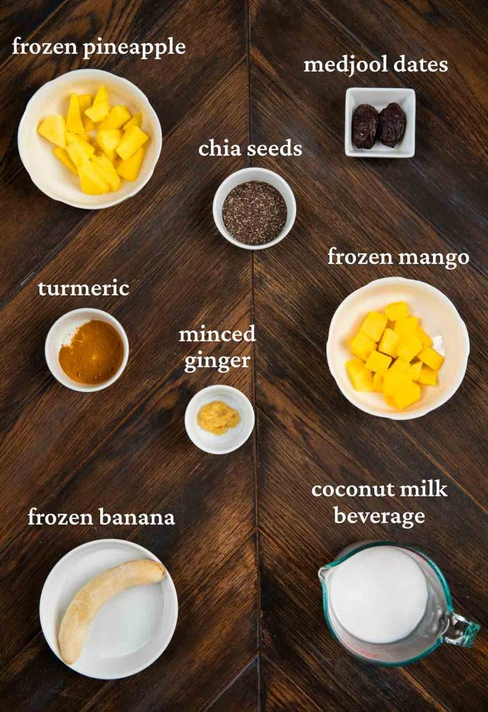 An overhead shot showing the ingredients for a smoothie, including pineapple, dates, chia seeds, mango, turmeric, ginger, coconut milk, banana, and ginger.