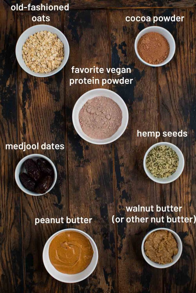 An image showing all of the ingredients for vegan protein balls; oats, cocoa powder, dates, protein powder, hemp seeds, and nut butters.