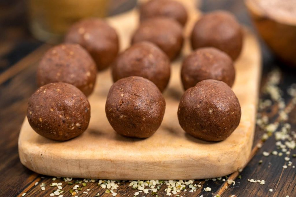 A cutting board with chocolate nut butter protein balls on top and hemp seeds sprinkled around.