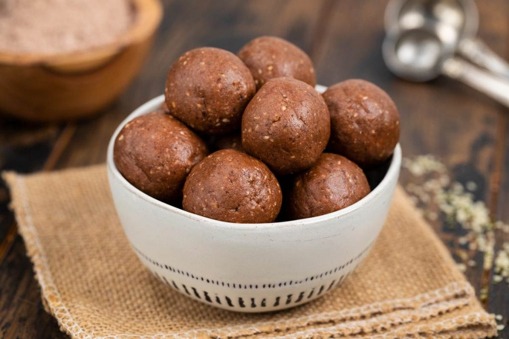 A bowl filled with chocolate nut butter protein balls on a burlap background.