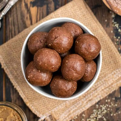 An overhead shot of a white bowl filled with chocolate nut butter protein balls on a burlap background.