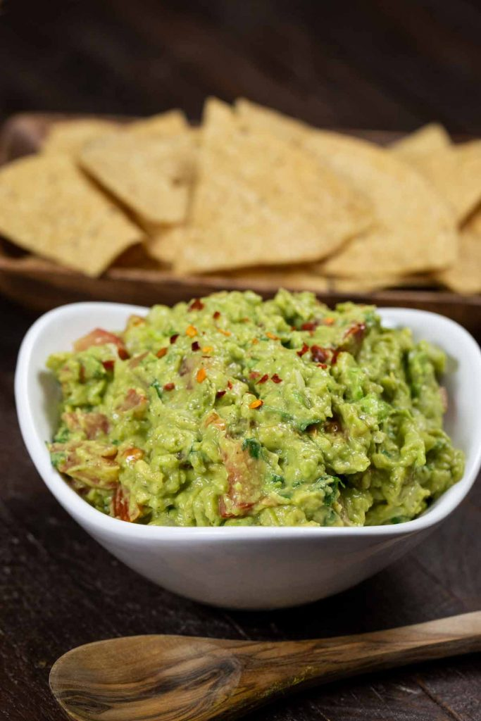 A closeup of a bowl of classic guacamole with a wooden spoon.