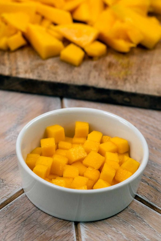 A small white bowl filled with diced mango, with chunks of mango in the background.