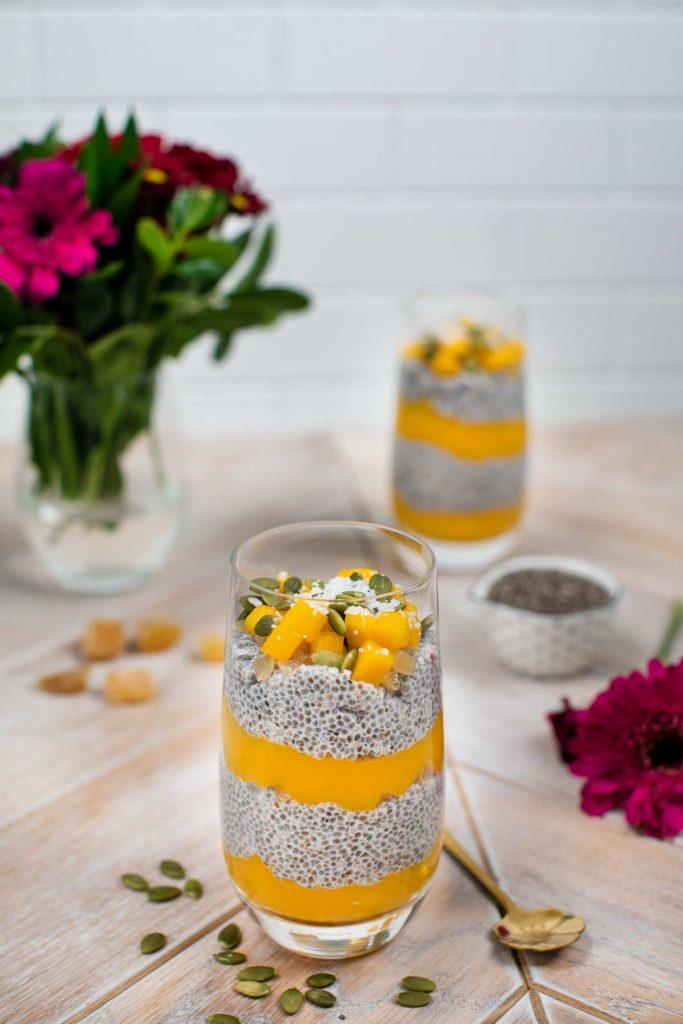 A bowl of mango chia seed pudding with chia seeds, flowers, and another bowl of chia seed pudding in the background.