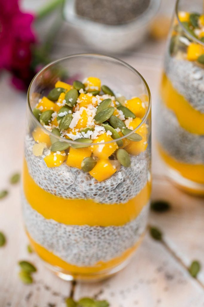 A closeup of a glass filled with mango chia pudding, topped with fresh mango, pumpkin seeds and shredded coconut.