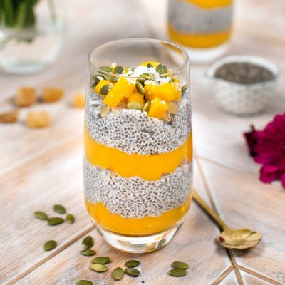 A mango chia seed pudding in a glass with pumpkin seeds and a spoon.