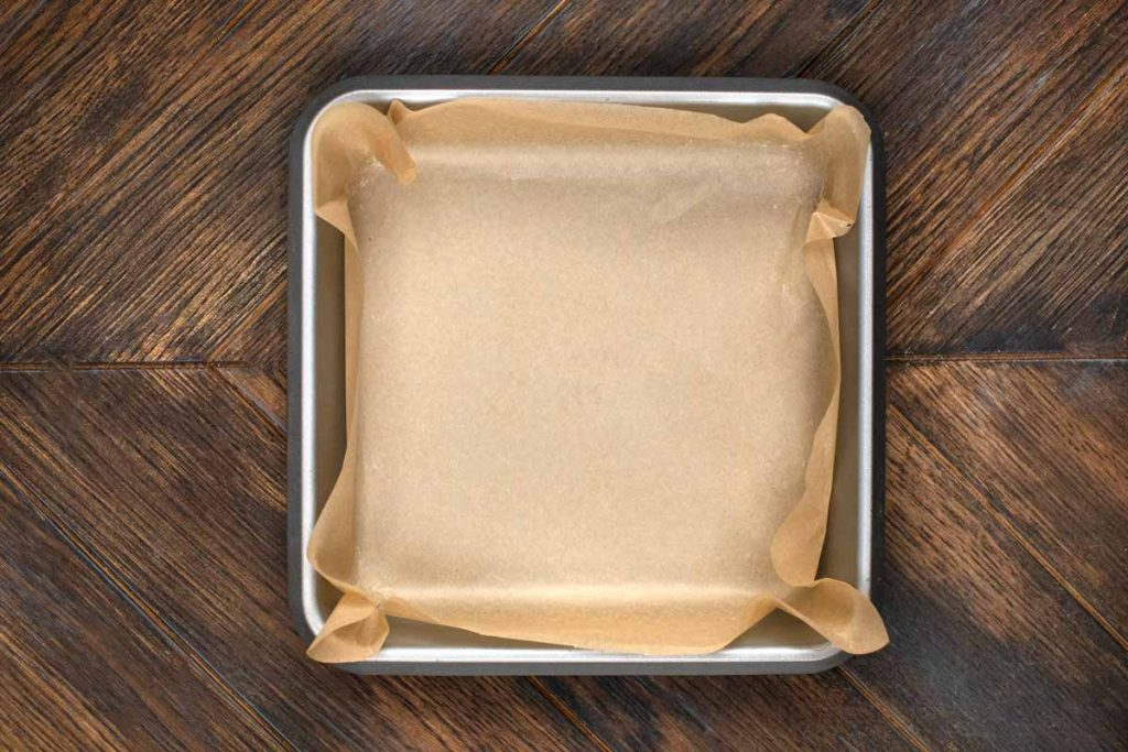 An overhead photo of an 8x8 baking pan covered in parchment paper.