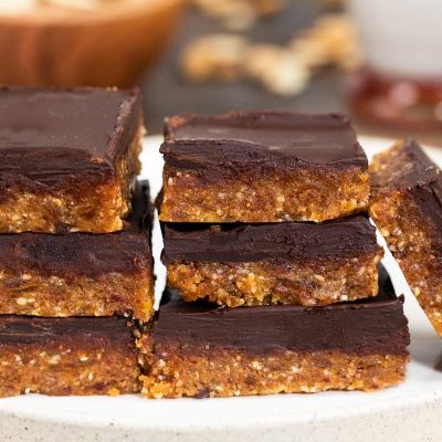 A plate of no bake vegan peanut butter chocolate bars, stacked on each other.
