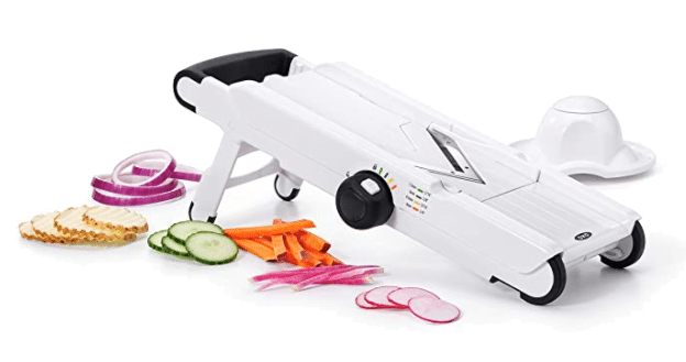 A mandoline with veggies on the side.