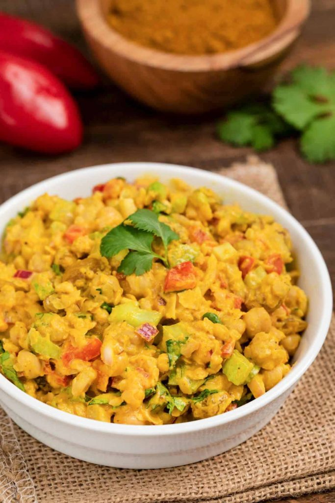 A bowl of curry chickpea salad, with a piece of fresh cilantro on top.