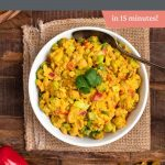 A white bowl filled with curry chickpea salad with peppers, golden raisins and herbs and spices on the side.