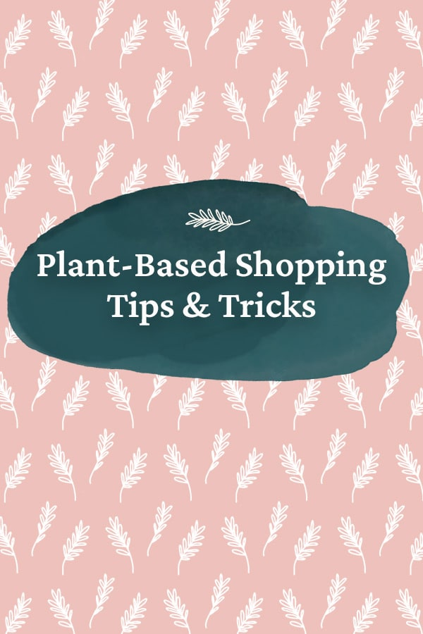 """A pink background with leaves and the words """"Plant Based Shopping Tips and Tricks"""" on a dark blue shape."""