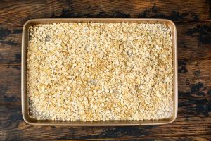 A baking pan covered with oats and walnuts.