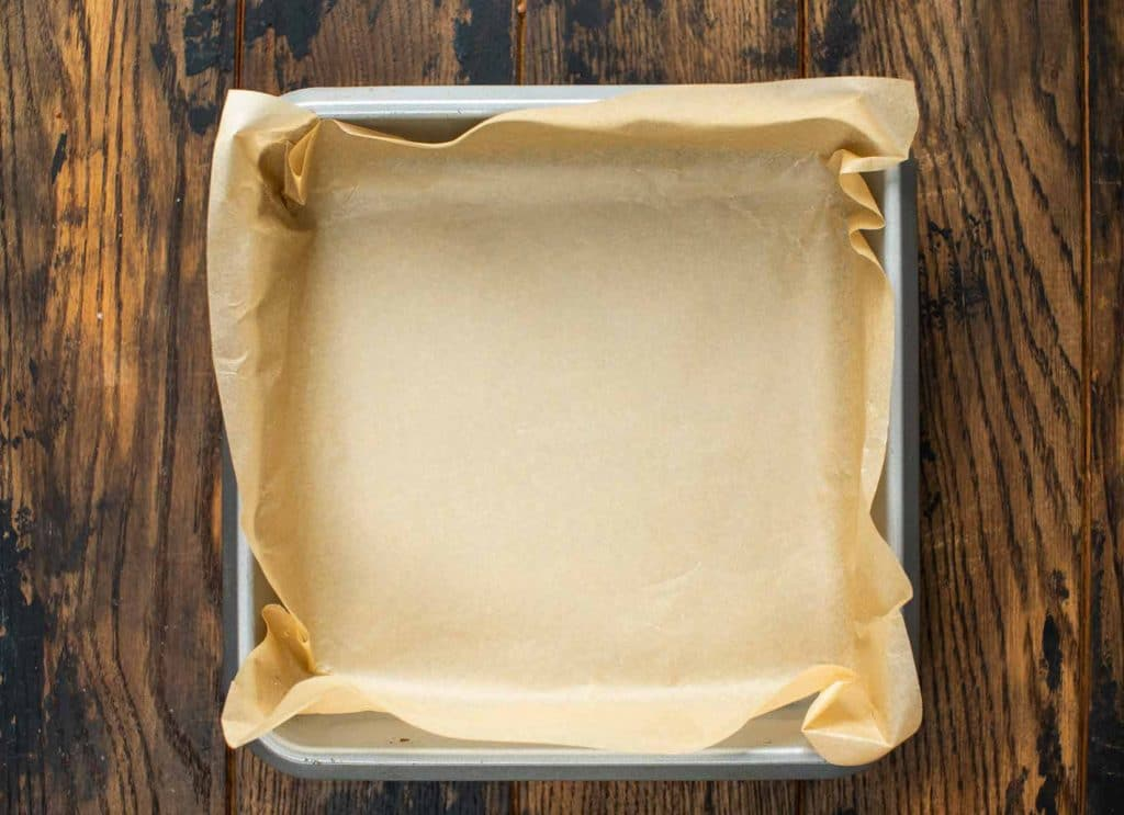 A 8x8 baking pan with parchment paper.